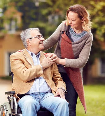 Caregiver and an elder man in a wheelchair smiling at each other
