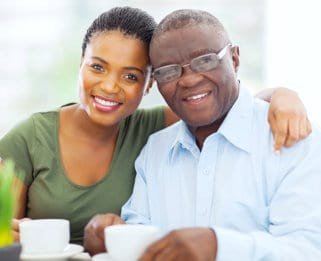 Caregiver and an elder man with glasses smiling