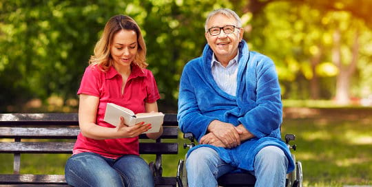 Caregiver is reading a book for the elder man
