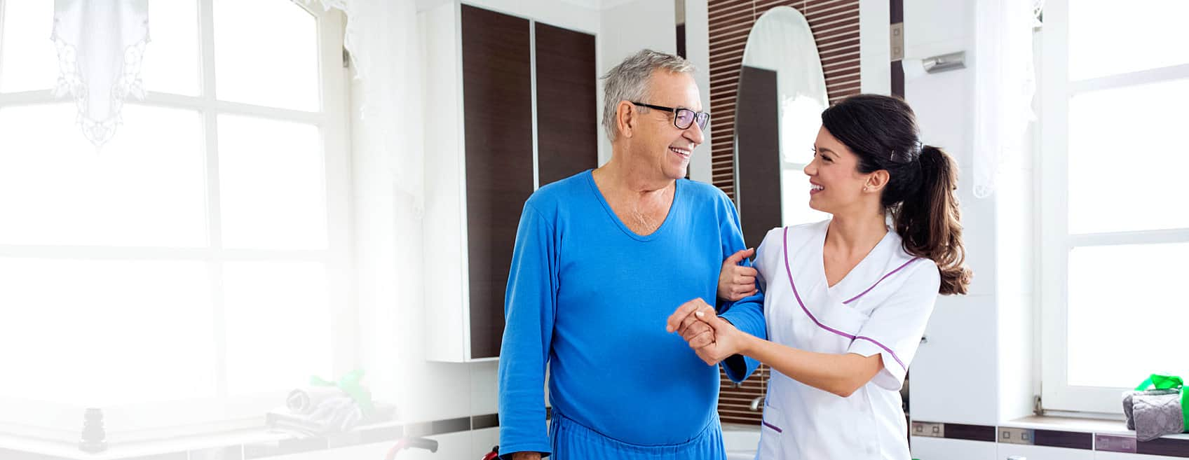 Caregiver and an elder man smiling at each other