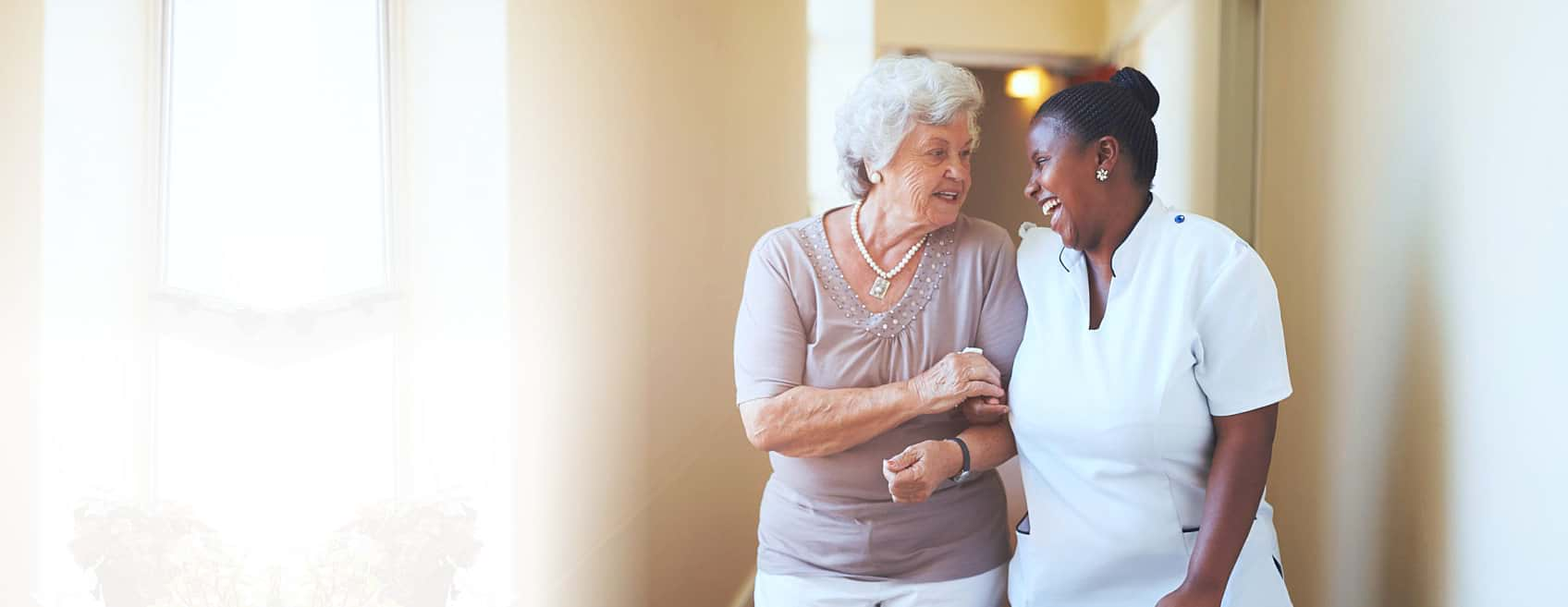 Caregiver and an elder womman smiling at each other
