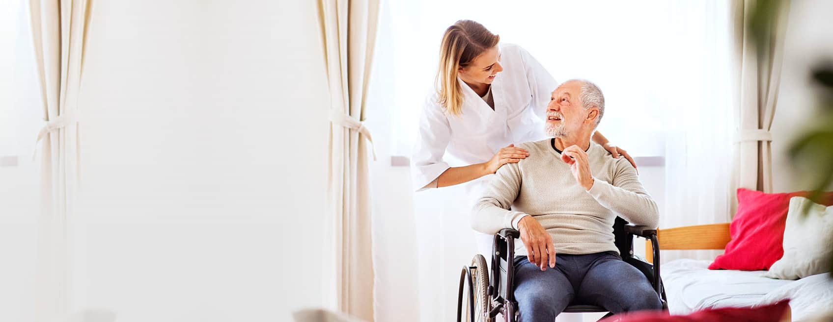 Caregiver and an elder man in a wheelchair both smiling