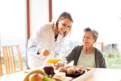 Caregiver serving the elder woman her meal