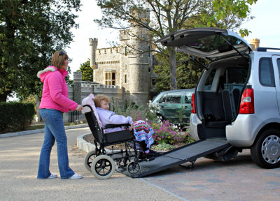 Caregiver pushing the elder woman in a wheelchair getting inside the van