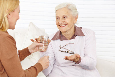 Caregiver offering the elder woman a glass of water to drink