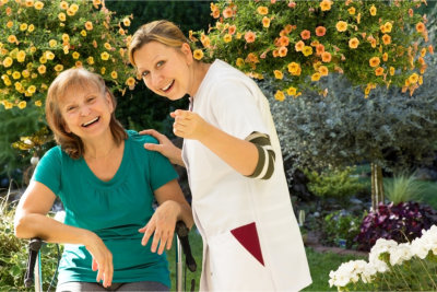 Caregiver telling the elder woman to smile at the camera