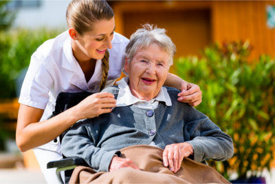 Caregiver and an elder woman in a wheelchair smiling