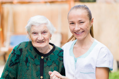 Caregiver and an elder woman smiling at the camera